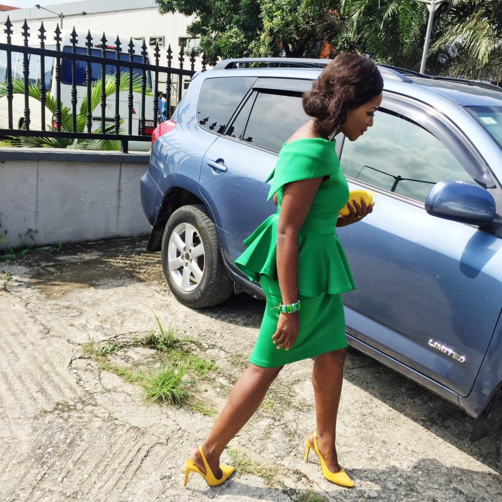 Lady wearing green peplum top and skirt paired with yellow shoes and purse